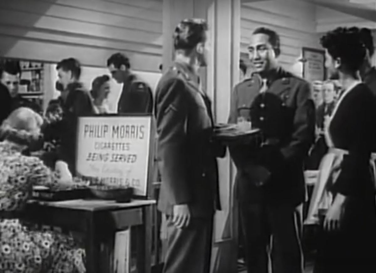 "A black soldier along with a black hostess in the ""Stage Door Canteen"" movie"