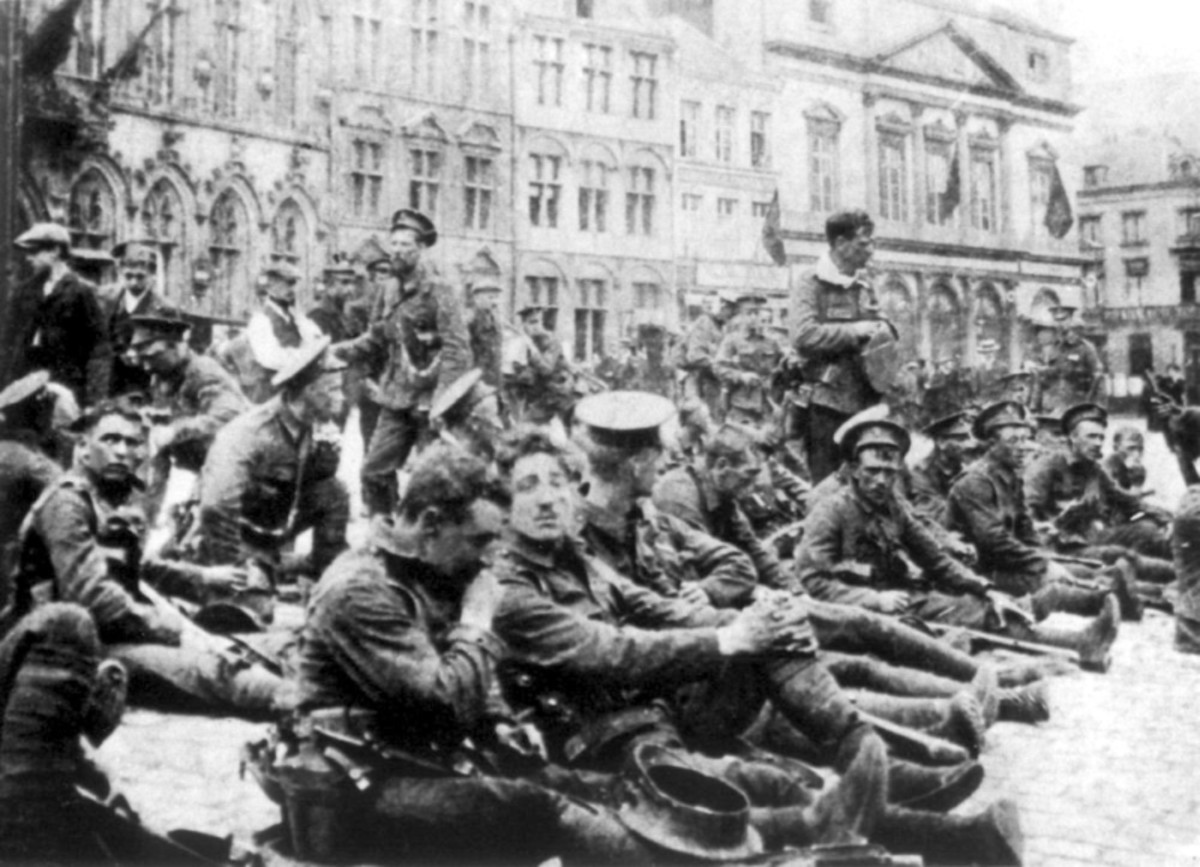 WW1: British soldiers resting in the square at Mons, waiting for the German First Army. August 1914. It would be 4 1/2 years and the last day of the war before Mons was retaken.