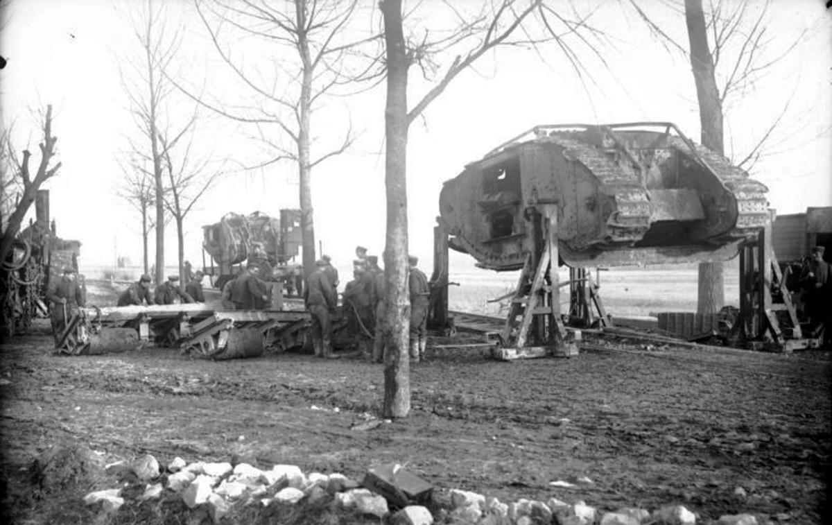 German soldiers prepare to load a British Mark I tank, captured at Cambrai, onto a flat bed rail car. Circa November 1917