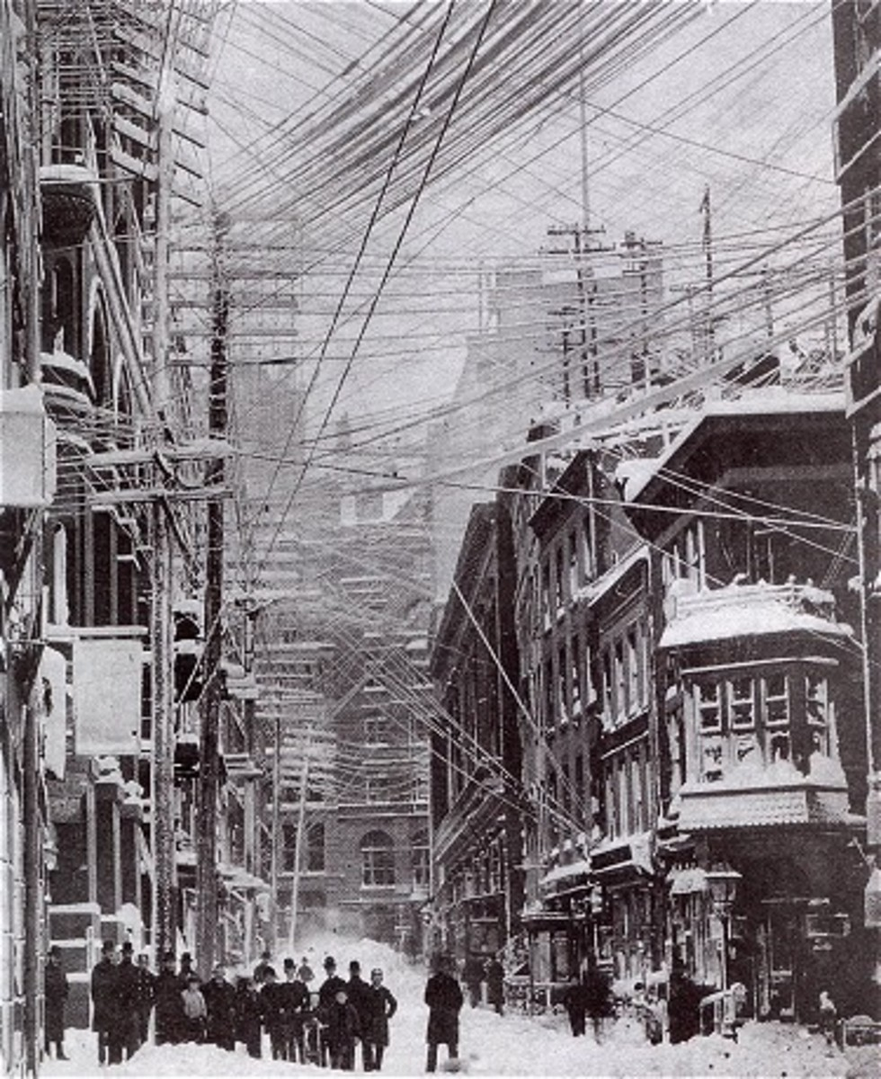 Photograph of a tangle of telephone, telegraph, and power lines above the streets of New York City after a major snow storm in 1888.