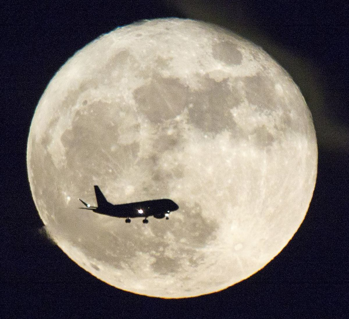 A jetliner is silhouetted against a Supermoon in Austin, Texas on November 14 in 2016, photo by Jay Godwin