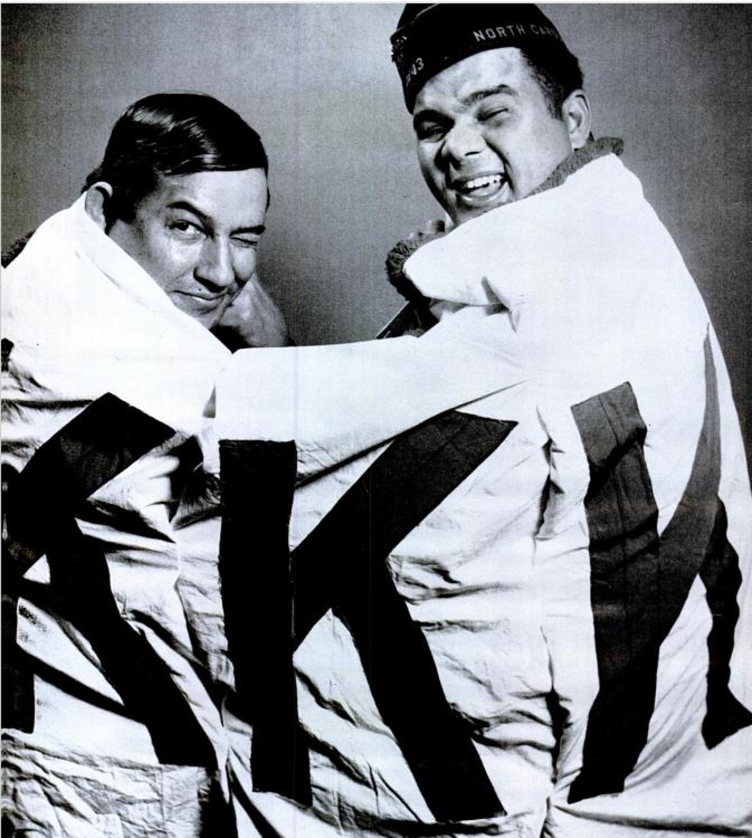 Simeon Oxendine and Charlie Warriax laugh while wearing the KKK banner taken away by the tribe