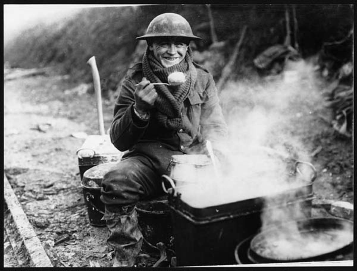 No wonder he looks happy as a soldier enjoys a rare hot meal, probably a potato.