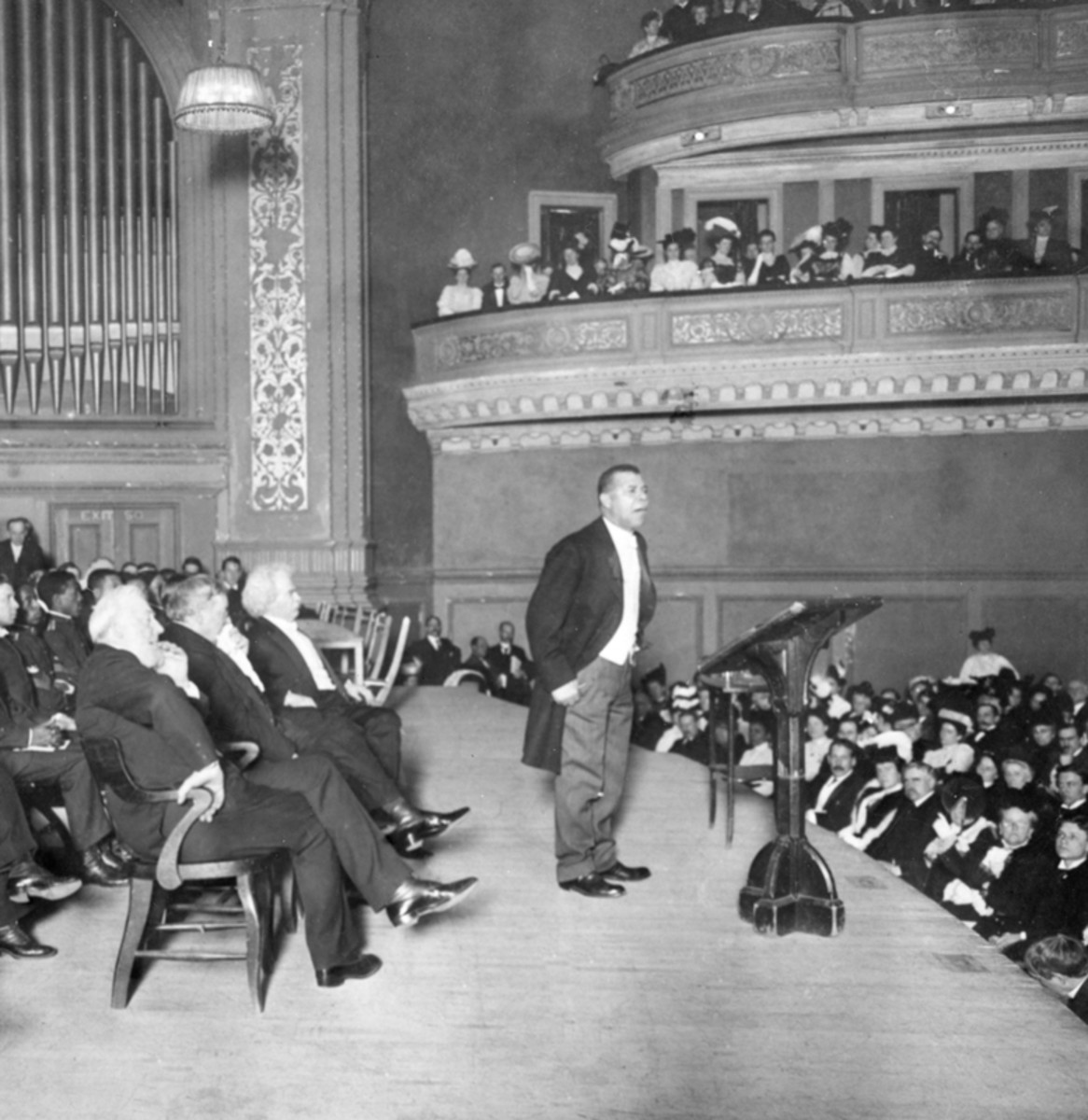 Booker T. Washington speaks at Carnegie Hall in 1906 with Mark Twain behind him listening.