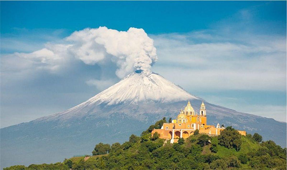 Popocatépetl in the background with La Iglesia de Nuestra Senora de los Remedios in the foreground.