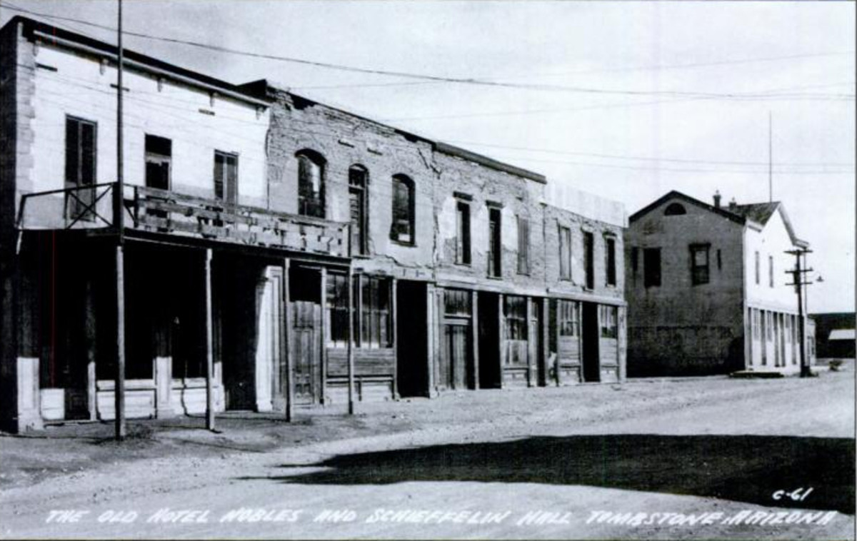 Front of City Hall in Tombstone - Located at 315 E. Fremont Street. City Hall is brick building with wooden balcony, with an adobe building on right.