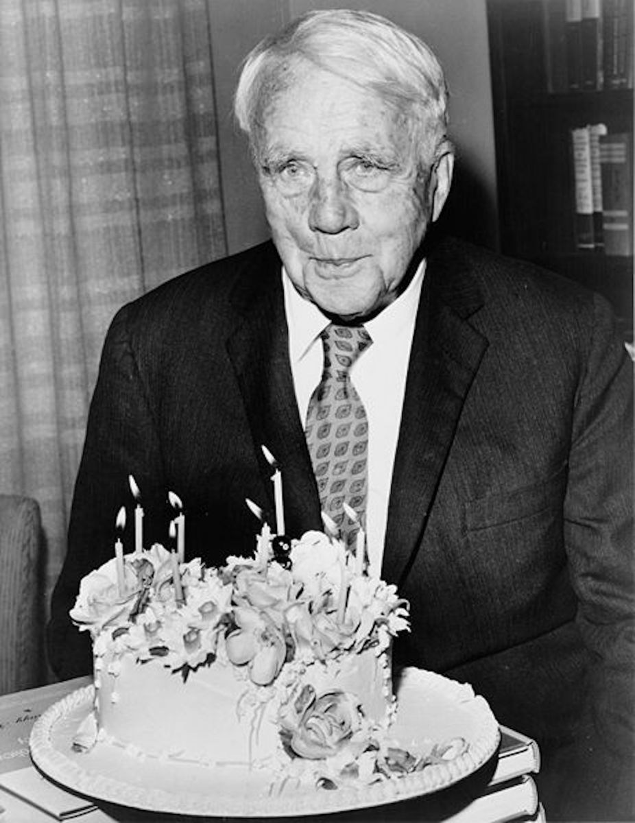 Robert Frost, poet poses with his birthday cake on his 85th birthday