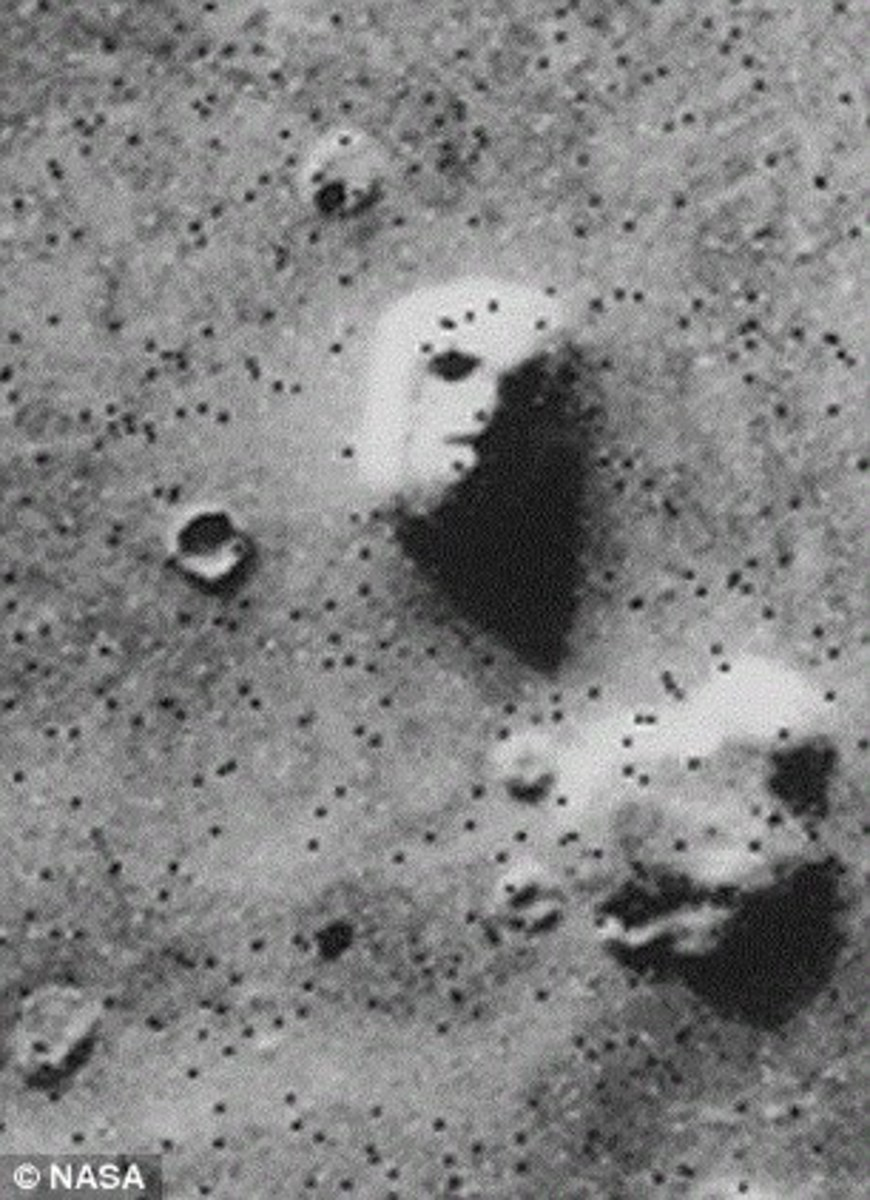 A satellite photo of a mesa in Cydonia, often called the Face on Mars. Later imagery from other angles did not include the shadows.