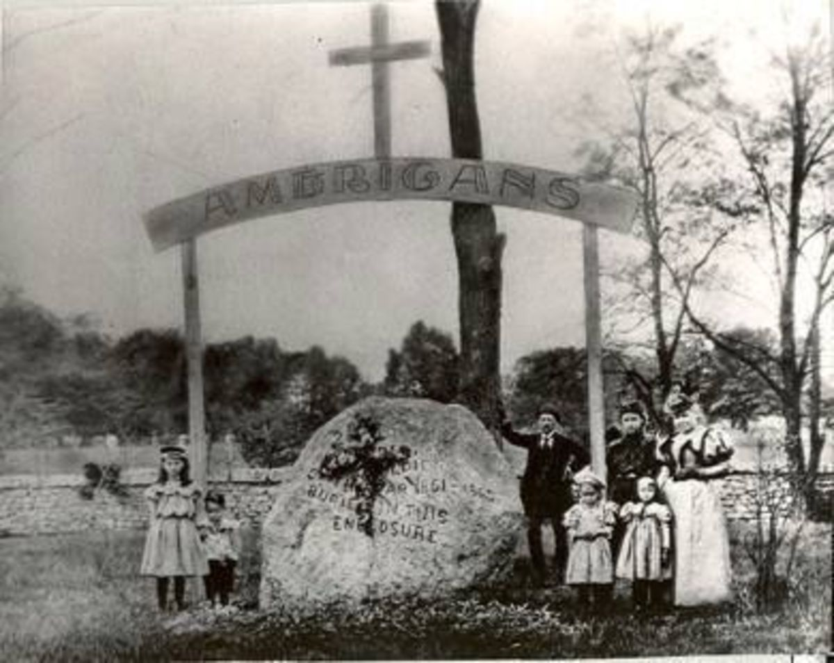 """Americans"" -- Original monument at the cemetery before the statue was installed. Teh same stone can be seen today, marking the passing of 2260 men. Pictured is Louisiana Briggs and her family visiting just after the war."