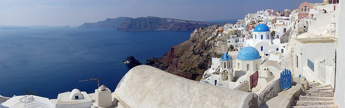 The whitewashed architecture of the Greek Islands attracts visitors from all over the world. Less noticeable is the great body of water on the left, which is actually an ancient caldera