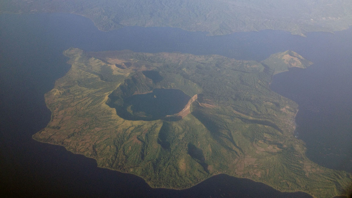 This aerial photo clearly depicts the water-filled caldera from an ancient  supervolcano eruption. Today, the body of water is known as Lake Taal.