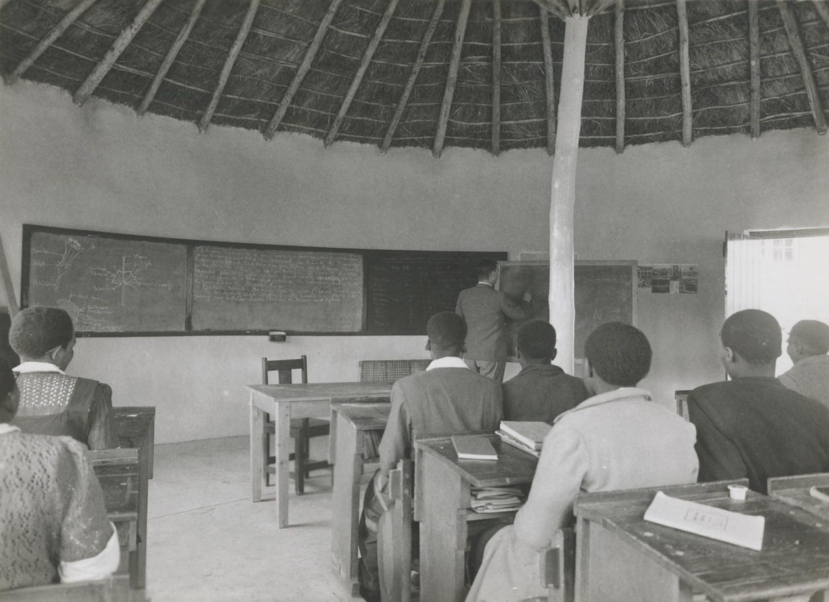 A High School class in session inside one of the rondavels. Teacher at the blackboard is my father, Murray McGregor