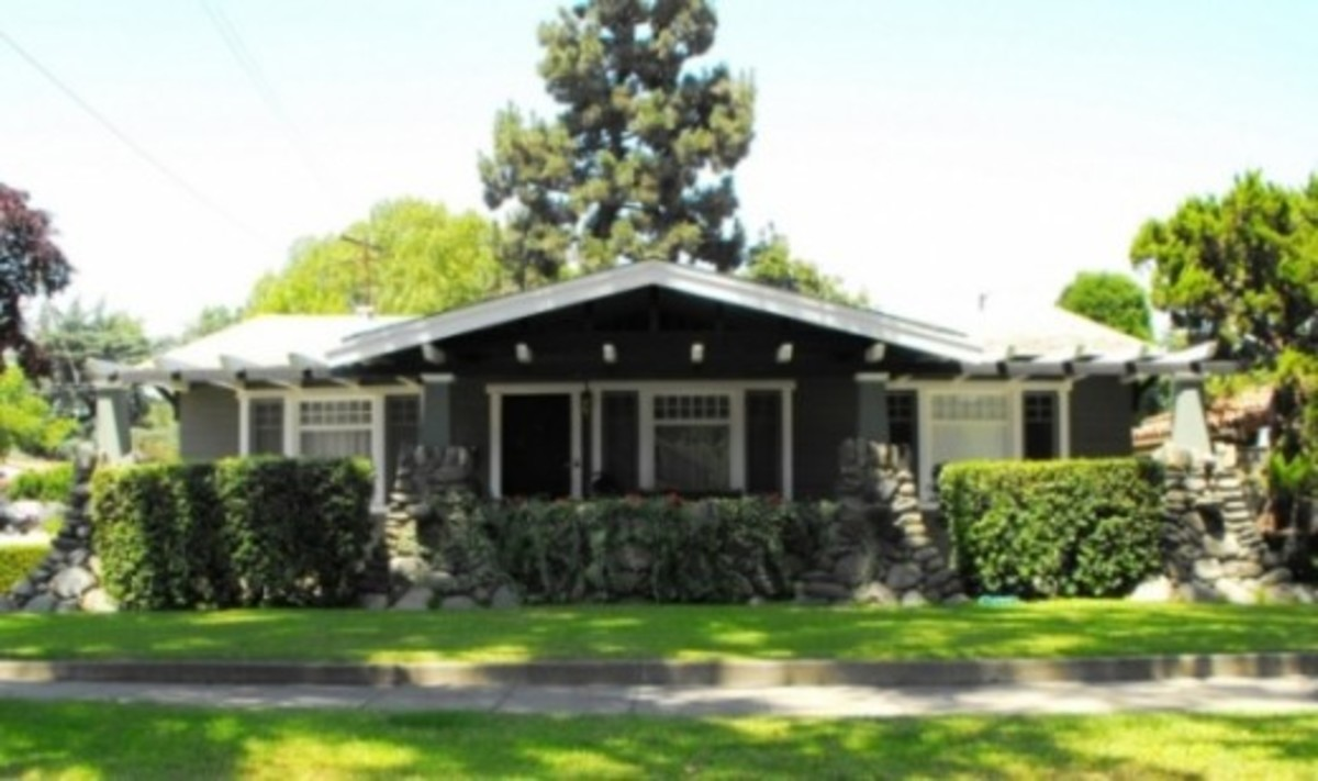 The effect of the river rock stone coming out of the ground to support a low house with jutting beam trim is classic arts and crafts on this California bungalow.