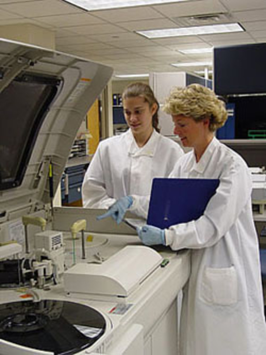 A typical analyzer in the chemistry department. Here you can see a new tech or maybe a student receiving some training. Every time the lab gets a new analyzer, we must go through training to learn how to use it.