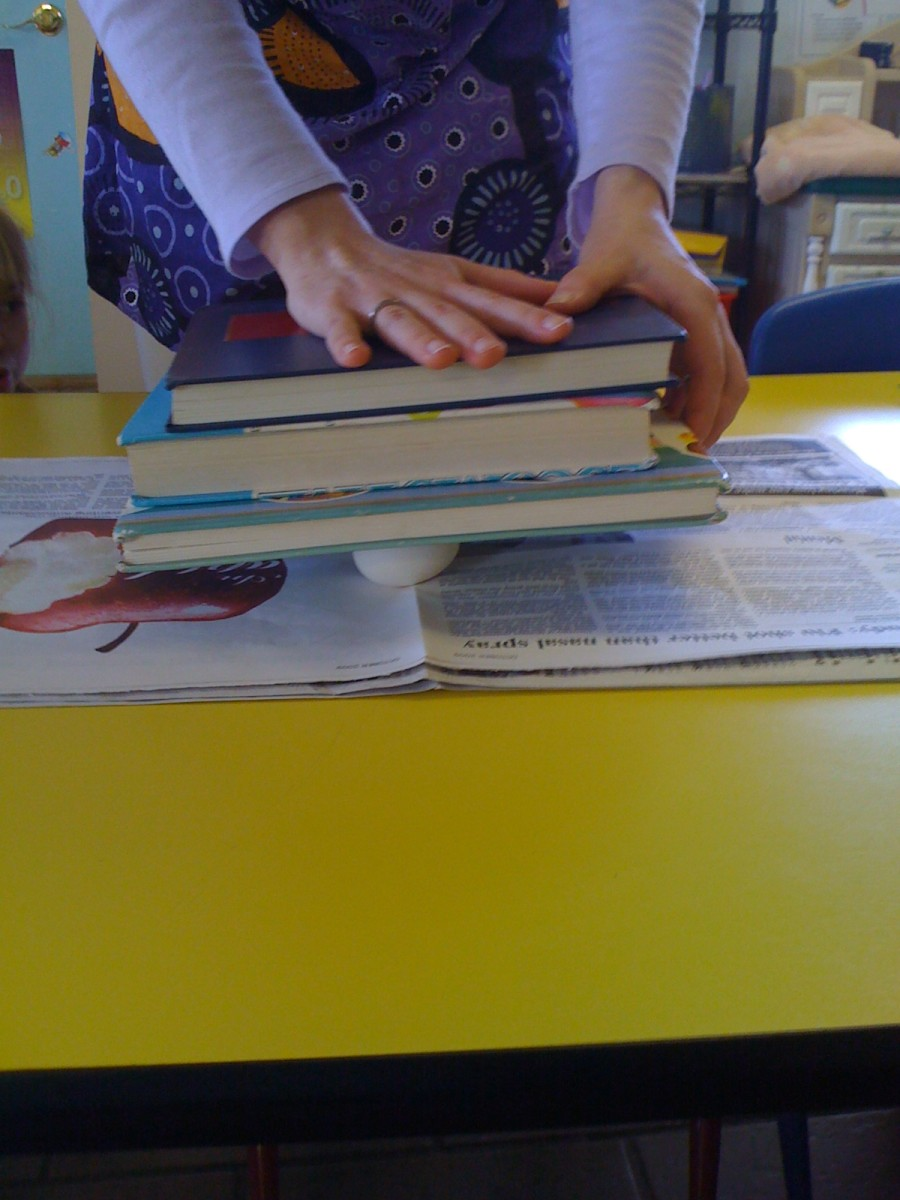 Eggshells supporting books.