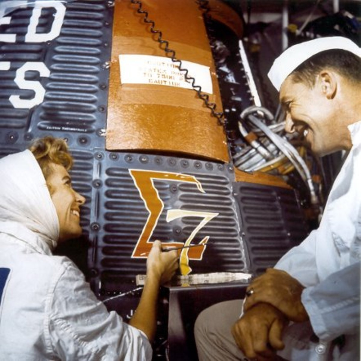 Wally Schirra observes as Cece Bibby paints the Sigma 7 logo. Photo courtesy of NASA.