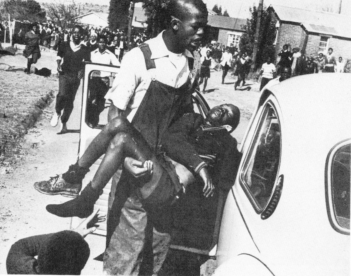 A rare picture of the limp body of Hector Petersen being carried by Mbulelo to a waiting vollksie