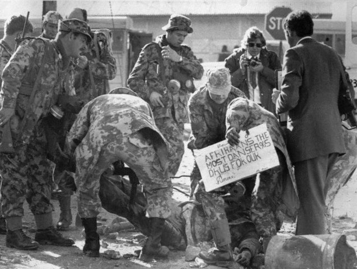 Camouflage riot police personnel with an injured person and his placard