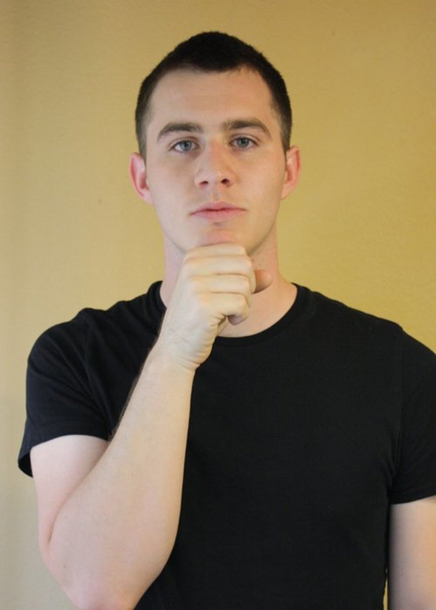 A closed fist is held to the chin and slightly opens and closes.