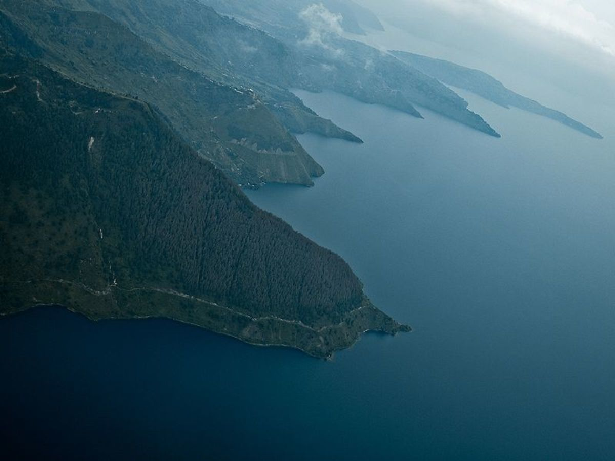"The southeast shore of Lake Toba, Indonesia; it is the remnant of a vast caldera blasted out of the surface about 73,000 years ago.  The debris may have caused years of volcanic ""winter,"" killing many creatures, including most early humans."