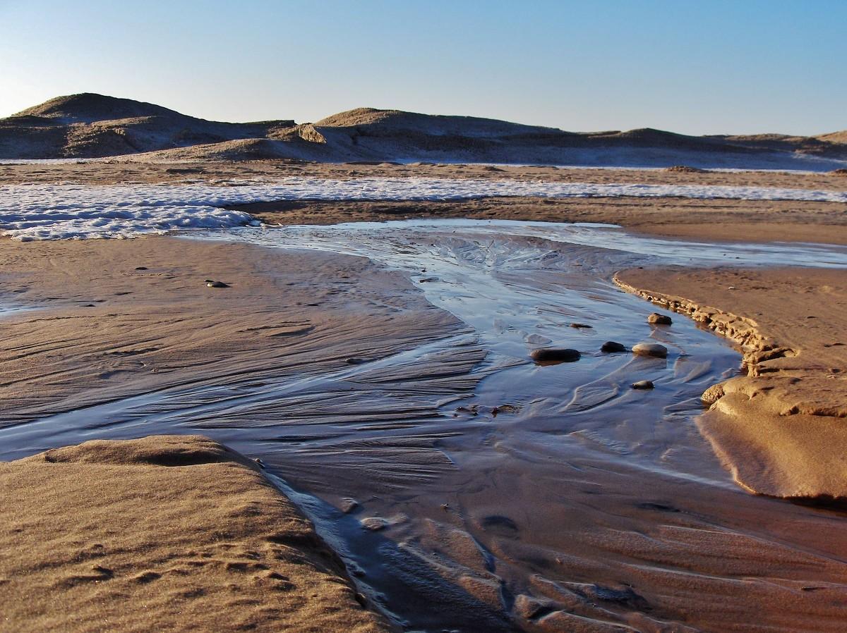 First melt of Lake Michigan ices shelf creates streams on the beach.