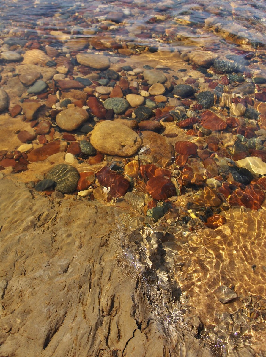 Brown Stones and more in Pier Cove Creek exposed during snow melt  by rushing water flow.