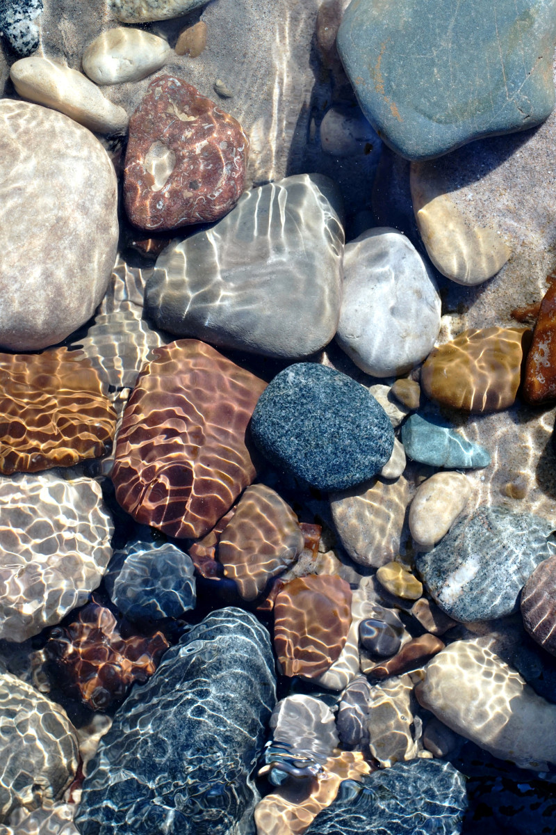Brown Stones, Basalt and more in Pier Cove Creek exposed during snow melt exposed by rushing water flow.