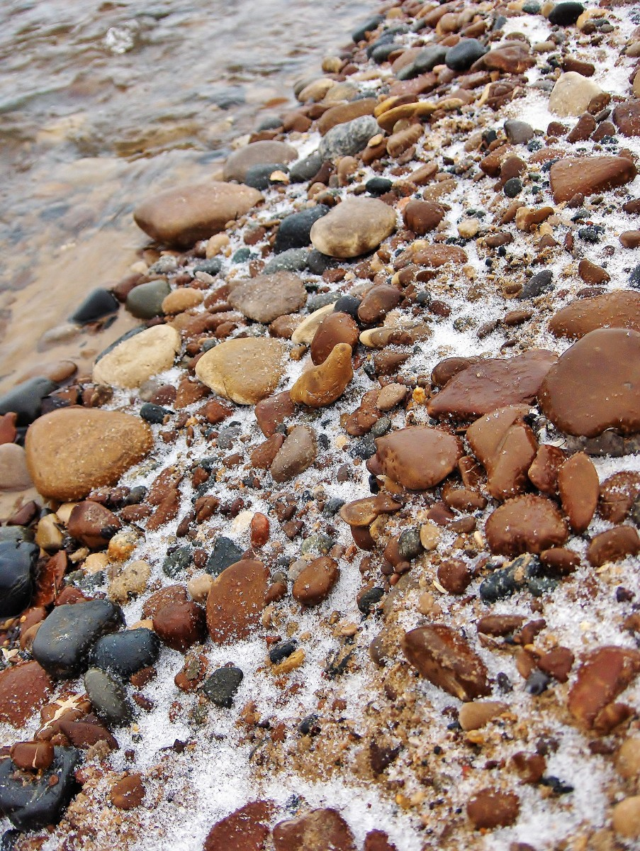 Snowfall illuminates brown stones from nuetral color of sand along the banks of Pier Cove Creek