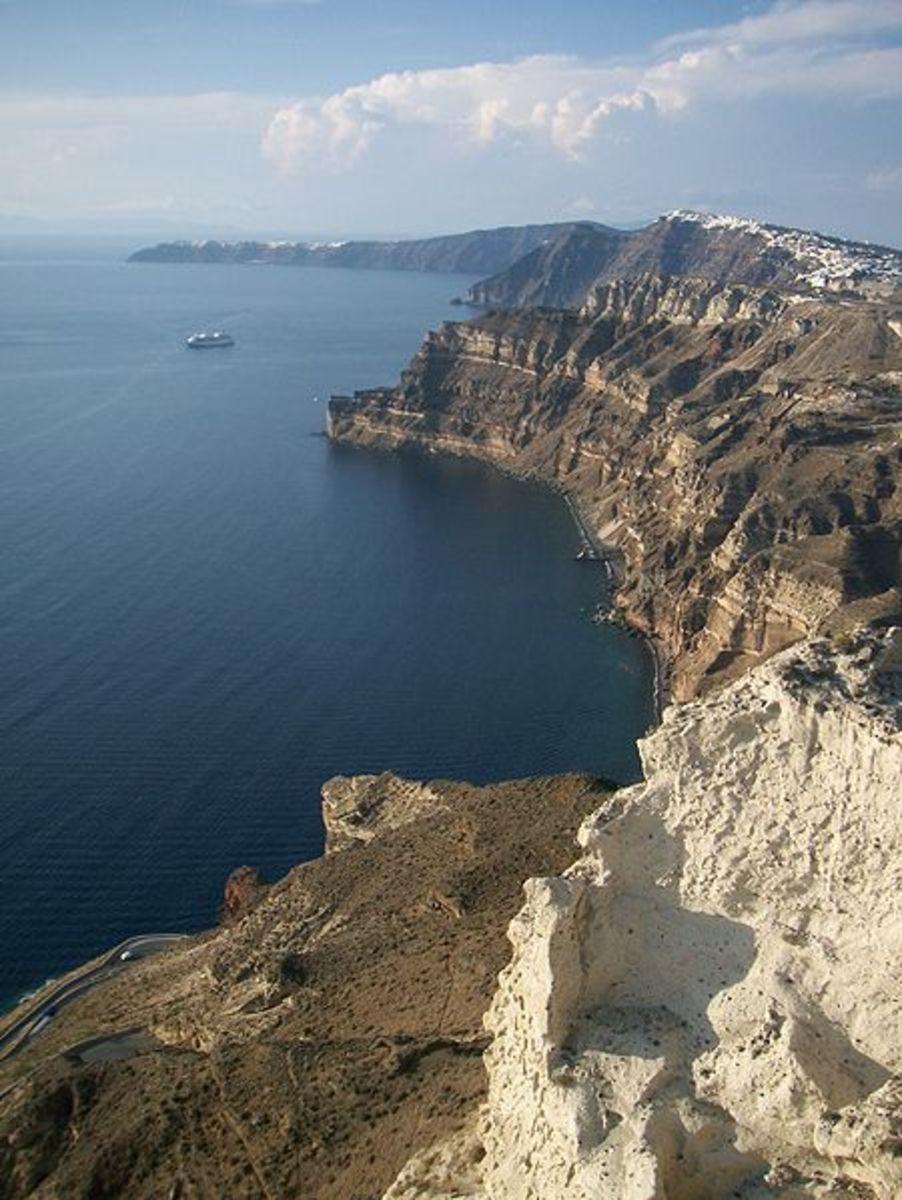 These 1000 foot tall cliffs curve around, forming the inner walls of a ring of islands comprising modern-day Santorini (Thera). They are what's left of the magma chamber of the ancient volcano that exploded, the cracked rim of a fiery cauldron!