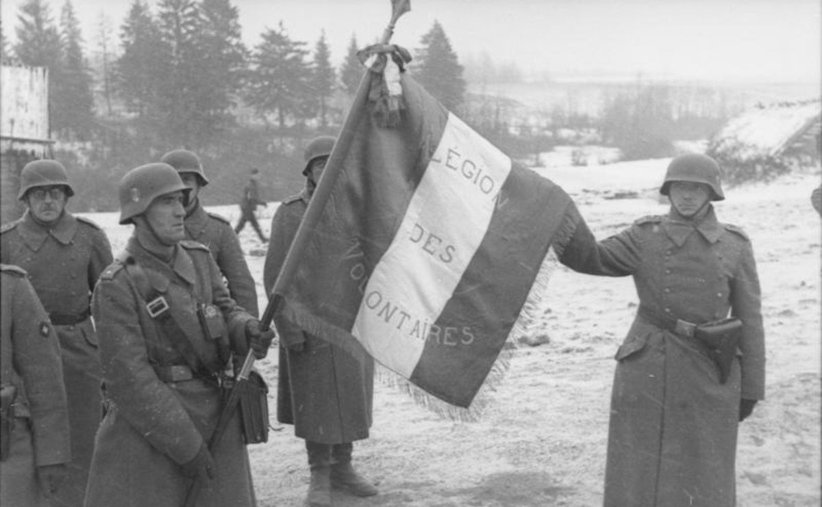 """French soldiers of the German """"Legion des Voluntaires"""" unit holding a French flag in Russia, 1941."""