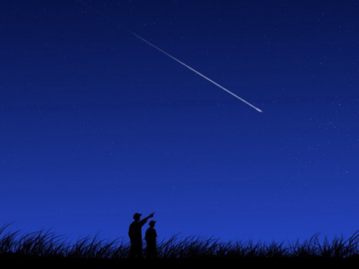 A shooting star creates a streak of light in the night sky