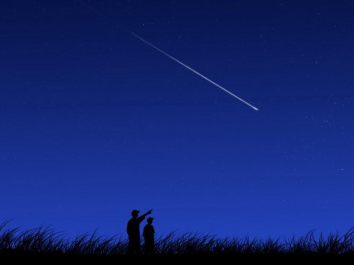 A shooting star creates a streak of light in the night sky