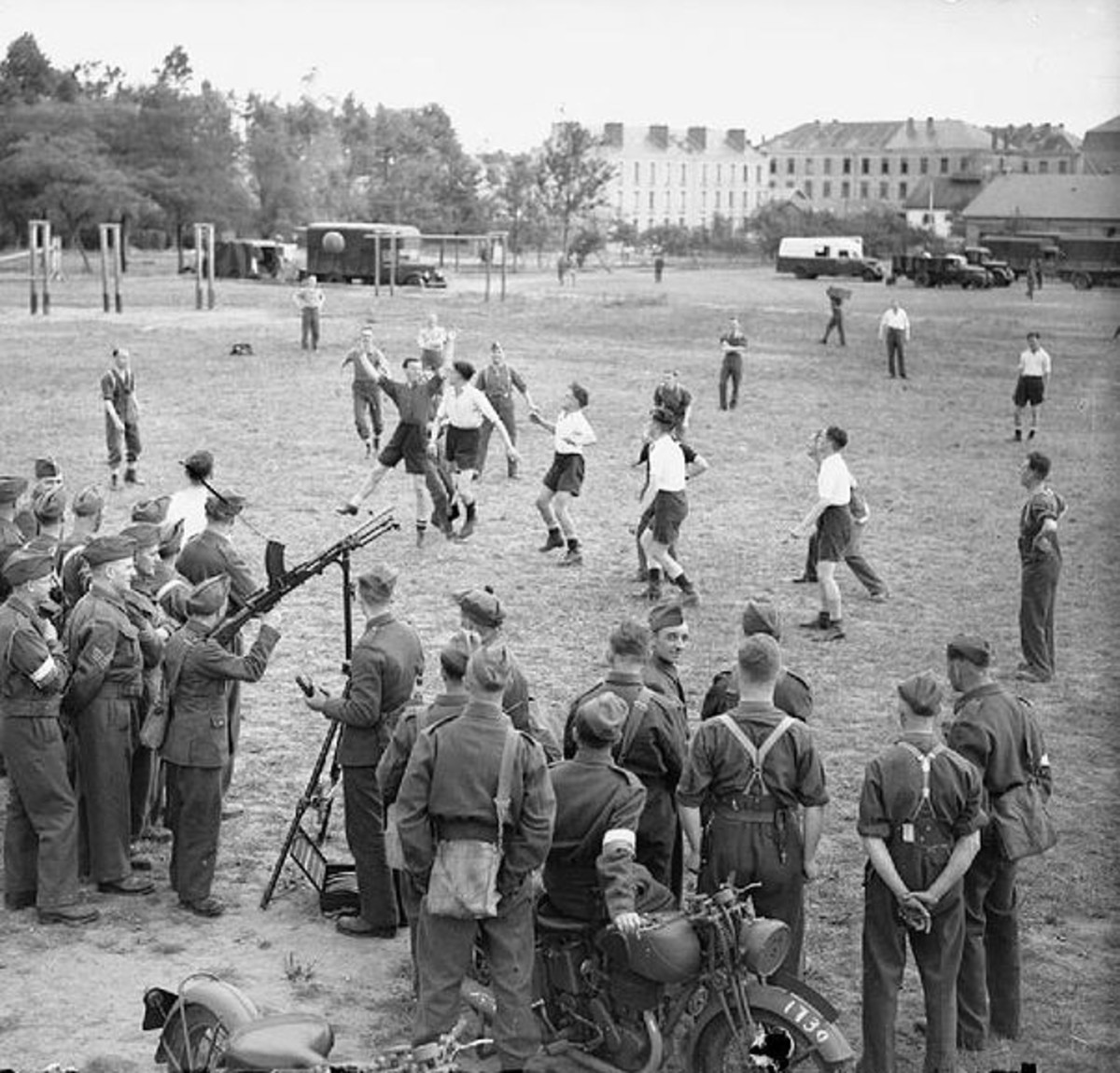 British soldiers playing football (soccer) in Le Mans, France during the Phoney War (1939-40). Note the gun mounted on a tripod in case the Germans attacked from the air.