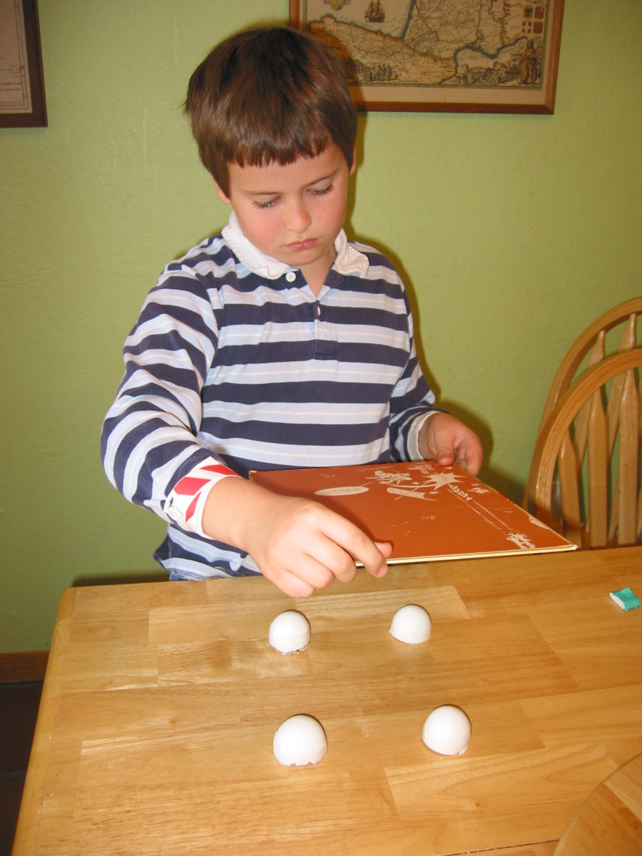 2. Put 4 half-eggshells in a square on a flat surface.