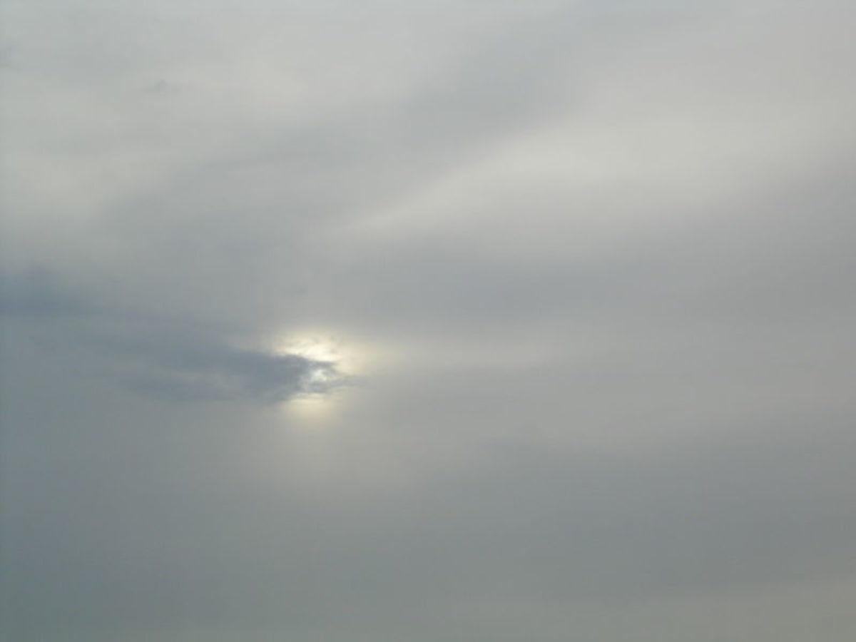 The sun shining through altostratus clouds