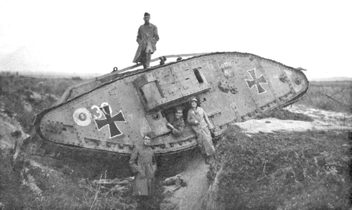 "Art Bell and Leah with captured Mark IV tank in WW1 battlefield. Original caption ""English tank - captured by Germans. Note - Bomb on ground. Hindenburg Line"""
