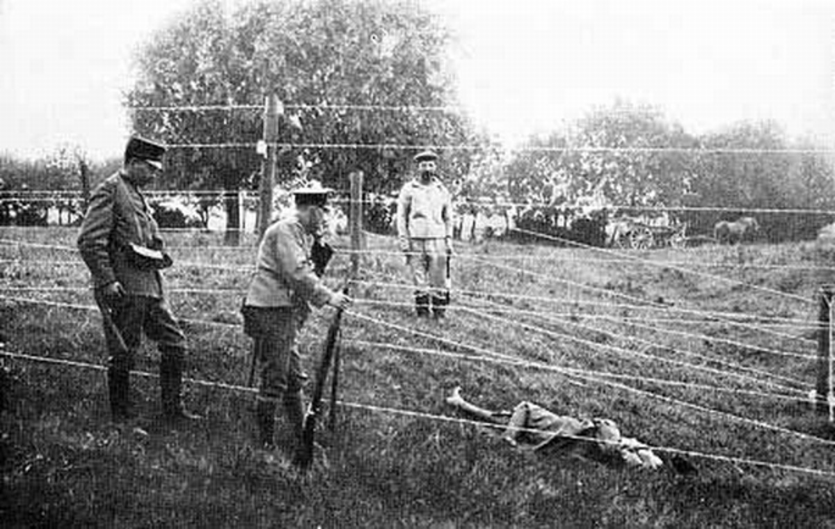 WW1: In the foreground soldiers of a Dutch border patrol. On the other side of the fence a German soldier. In between them a body lying under the deadly wire. To remove bodies the current had to be switched off.