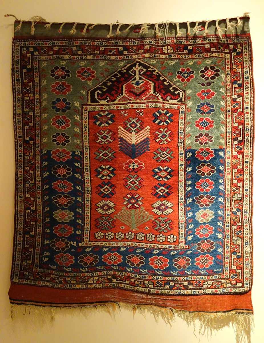 The niche at the top of the rug represents the mihrab and the direction of prayer.