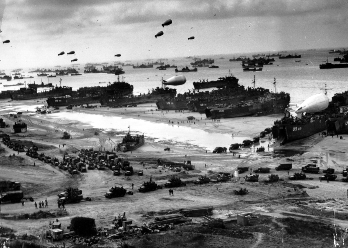 "WW2: Normandy Invasion, June 1944. Landing ships (LSTs) putting cargo ashore on one of the invasion beaches, at low tide. Note the barrage balloons overhead and Army ""half-track"" convoy forming up on the beach."