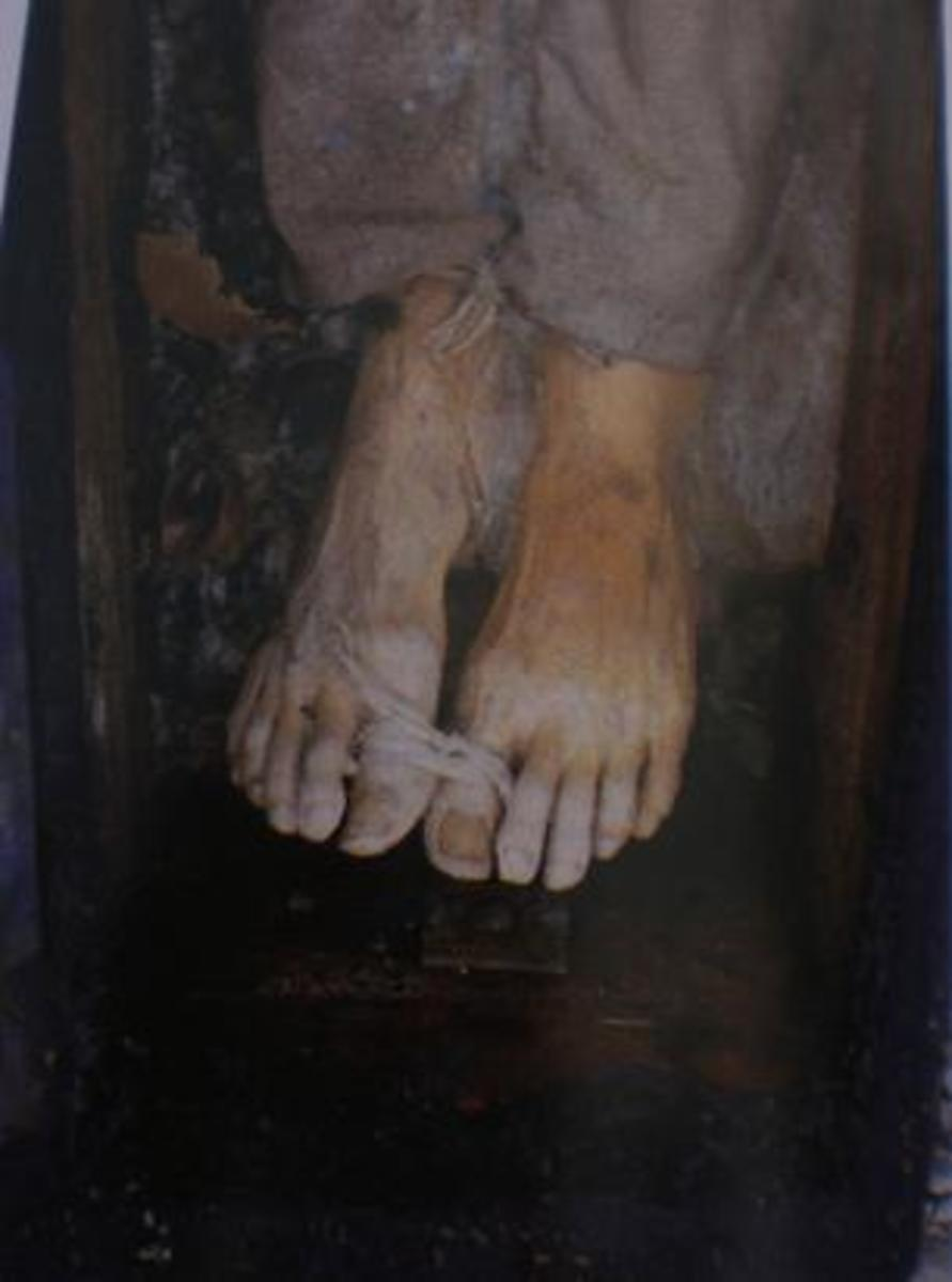 John's feet were lashed together shortly after his death for storage.