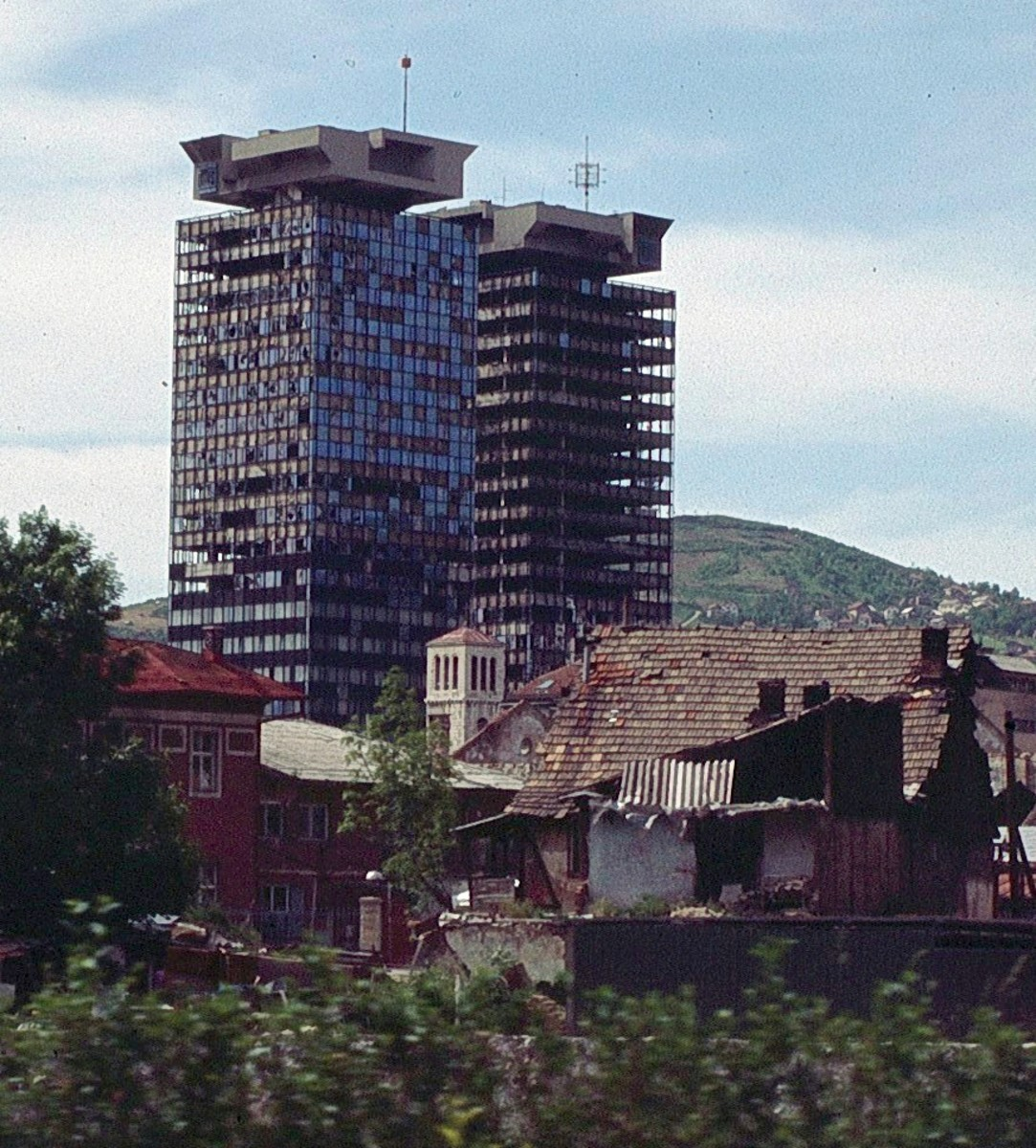 "Shelled by tanks, the UNITIC Twin Skyscrapers in Sarajevo were heavily damaged during the siege. Affectionately called ""Momo and Uzeir"" (two characters in a comedy show-- a Serb and a Bosnian), they remained standing, becoming symbols of resilience."