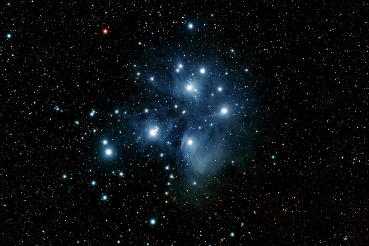 The Pleiades Star Cluster (described above). Sadly this degree of resolution will not be possible in binoculars, but the cluster remains one of the best binocular sights in the sky. The blue haze is a reflection nebula (described below)