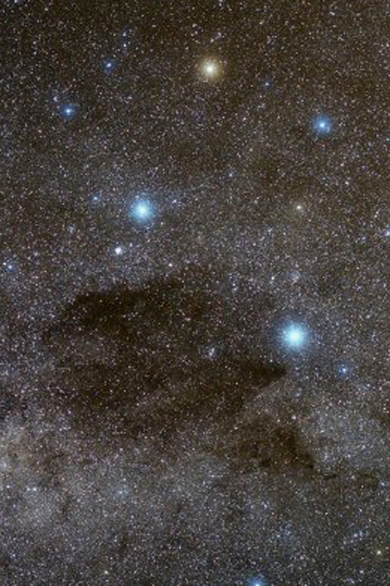 The Coalsack Dark Nebula visible against the bright glow of the Milky Way. The four brightest stars are the primary stars of the Southern Cross Constellation