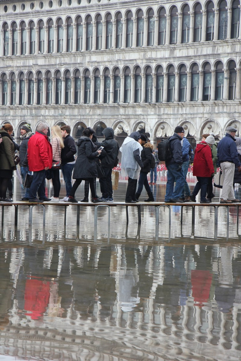 Venice, St. Mark's Square, flooded with water. People have to walk on the high-rise walkways.