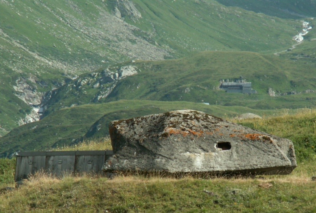 Camouflaged cannons and fortifications near Furka Pass in the Gotthard region. Note the fortress embedded in the hillside in the distance.