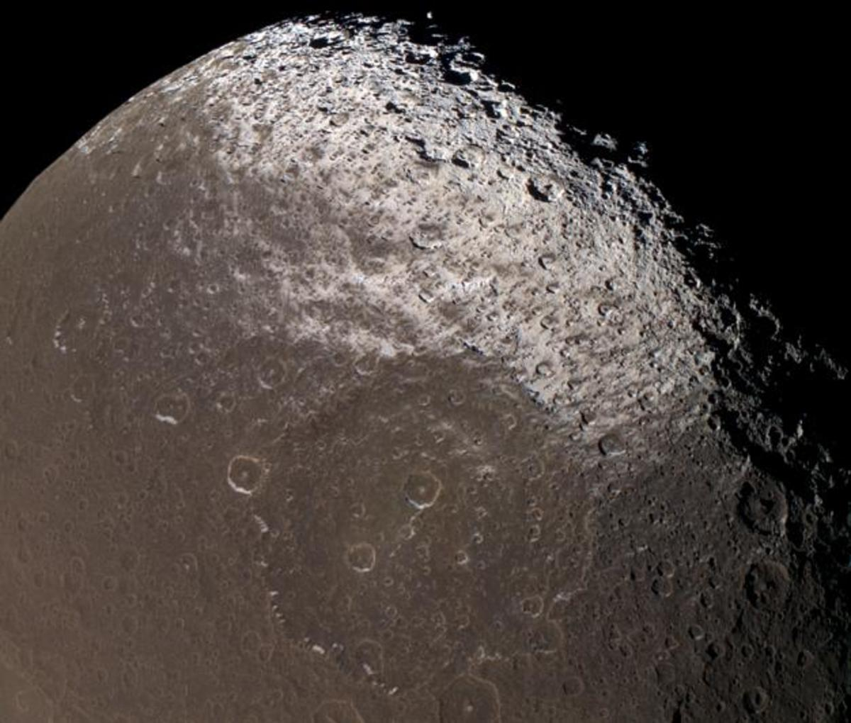 Saturn's moon Iapetus is a puzzle: its backside is light-colored, and its leading hemisphere is mostly coated with a muddy brown...something...that appears to have splattered it from another moon, the rings, or an unknown source.