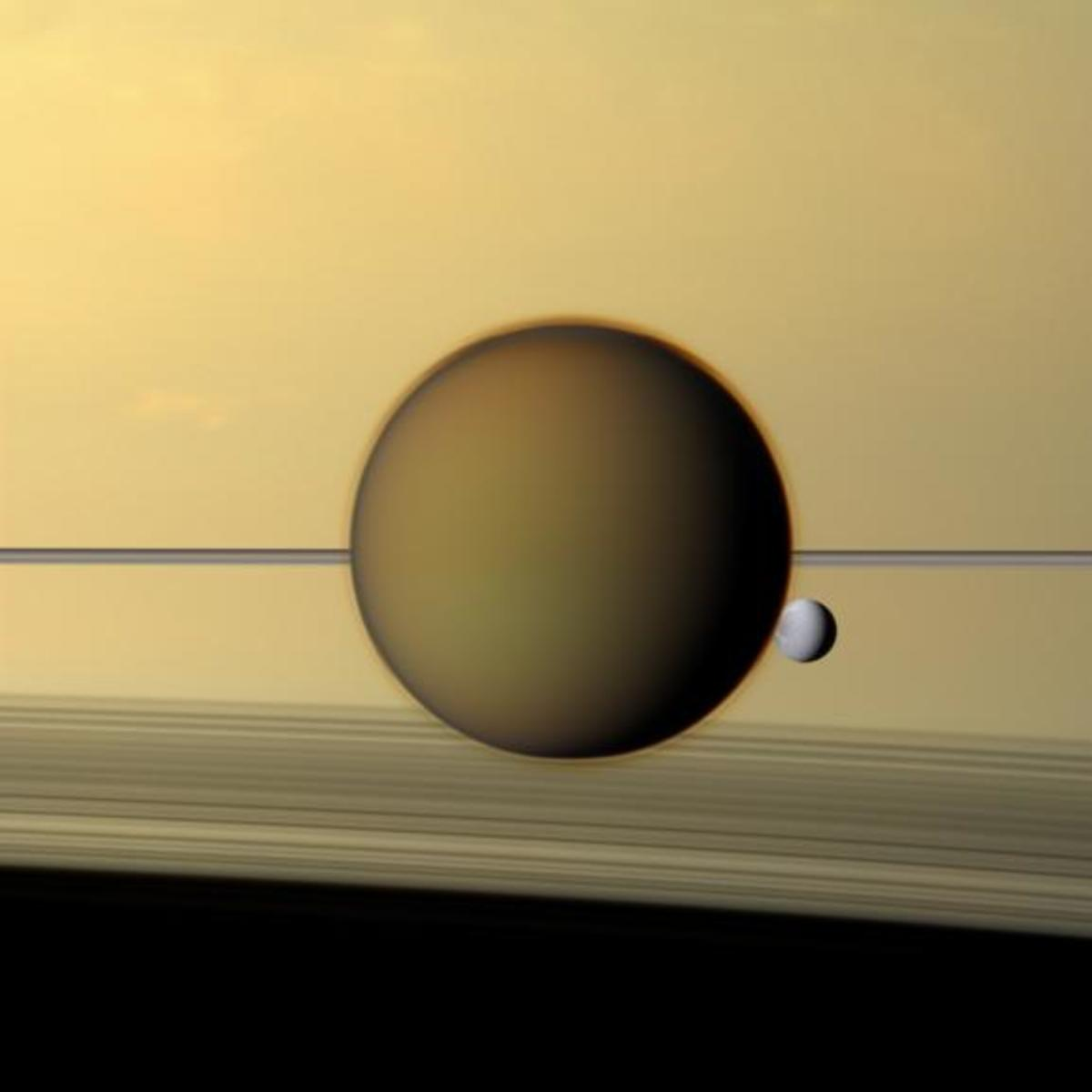Saturn's moon Titan, 3200 miles across, and Dione, 698 miles across, float against the backdrop of Saturn's cloud tops and rings. Look closely; you can see Titan's fuzzy atmosphere in front of Dione.