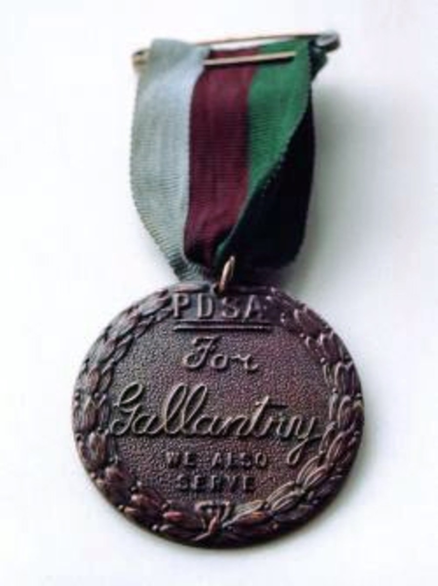 "The United Kingdom's PDSA Dickin Medal (obverse) which is awarded to animals for conspicuous gallantry or devotion to duty while serving in a military conflict. ""PDSA For Gallantry We Also Serve"""