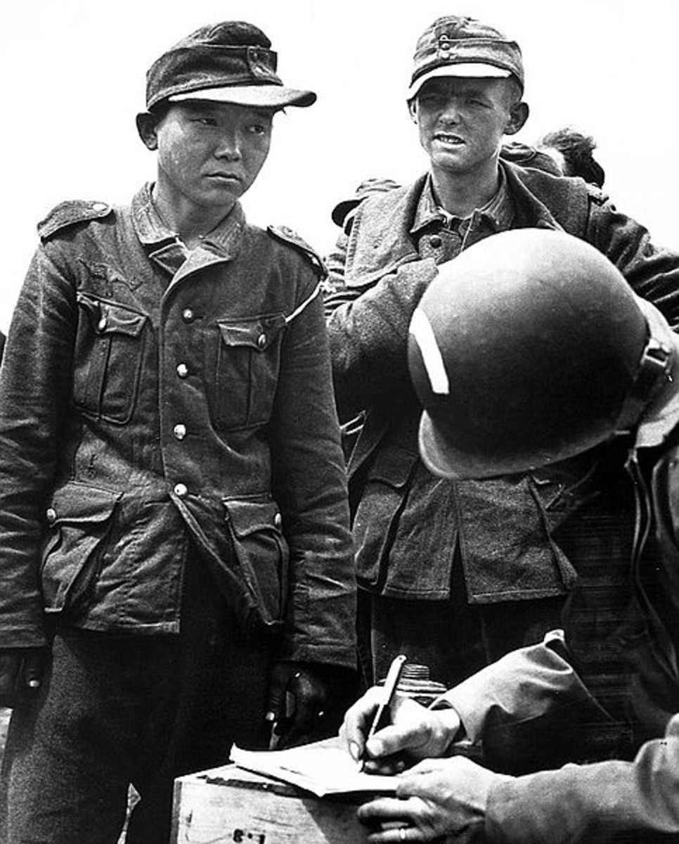 WWII: Yang Kyoungjong, an ethnic Korean soldier in the German Wehrmacht, captured by US Army soldiers in France after D-Day in June 1944. Date June 1944