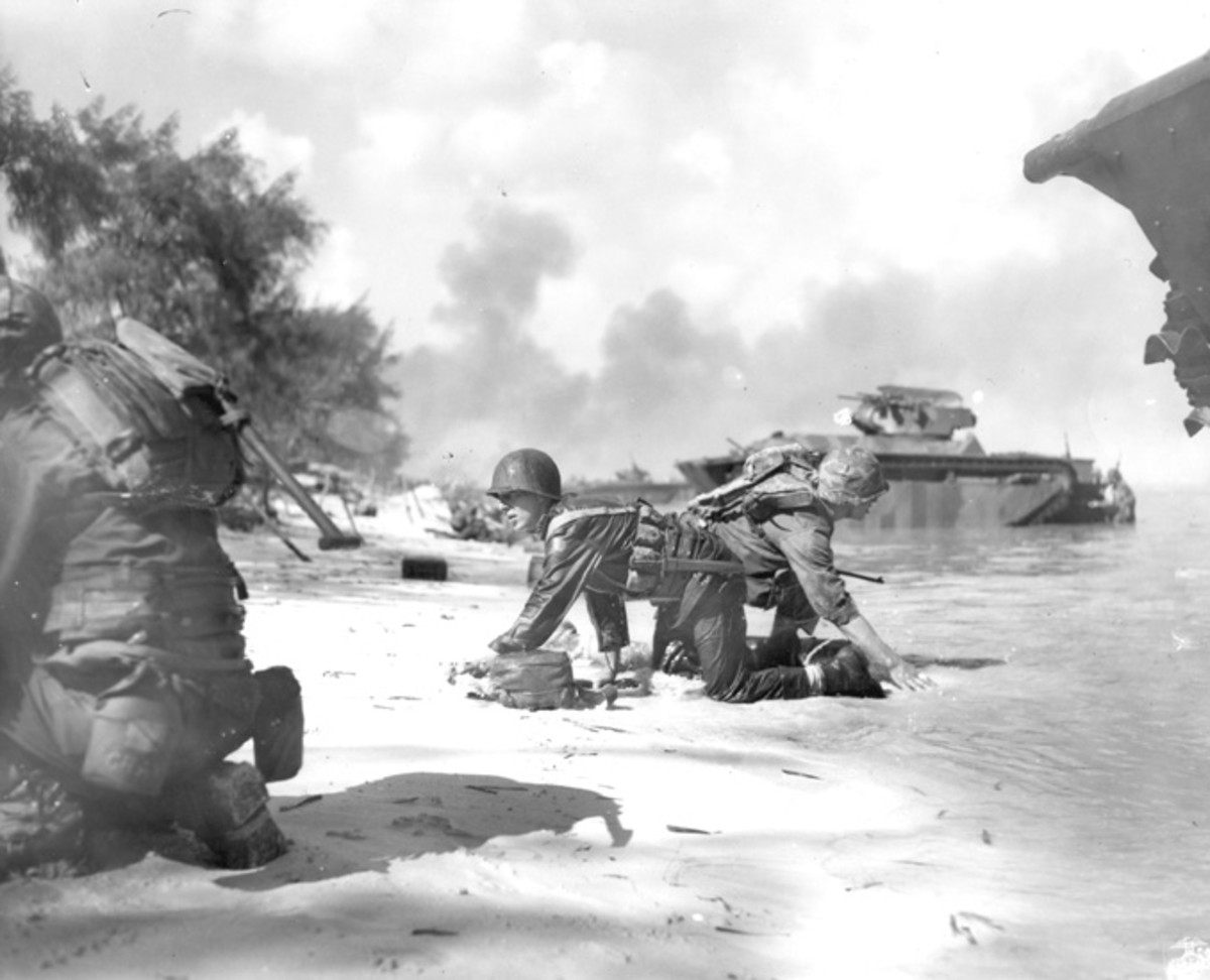 WW2: Saipan beachhead. Two Marines keep down low while they crawl to their positions as Japanese fire whines overhead. Their landing craft was hit by a Japanese mortar. In the background are Buffalos which supported the Marines in their landing.